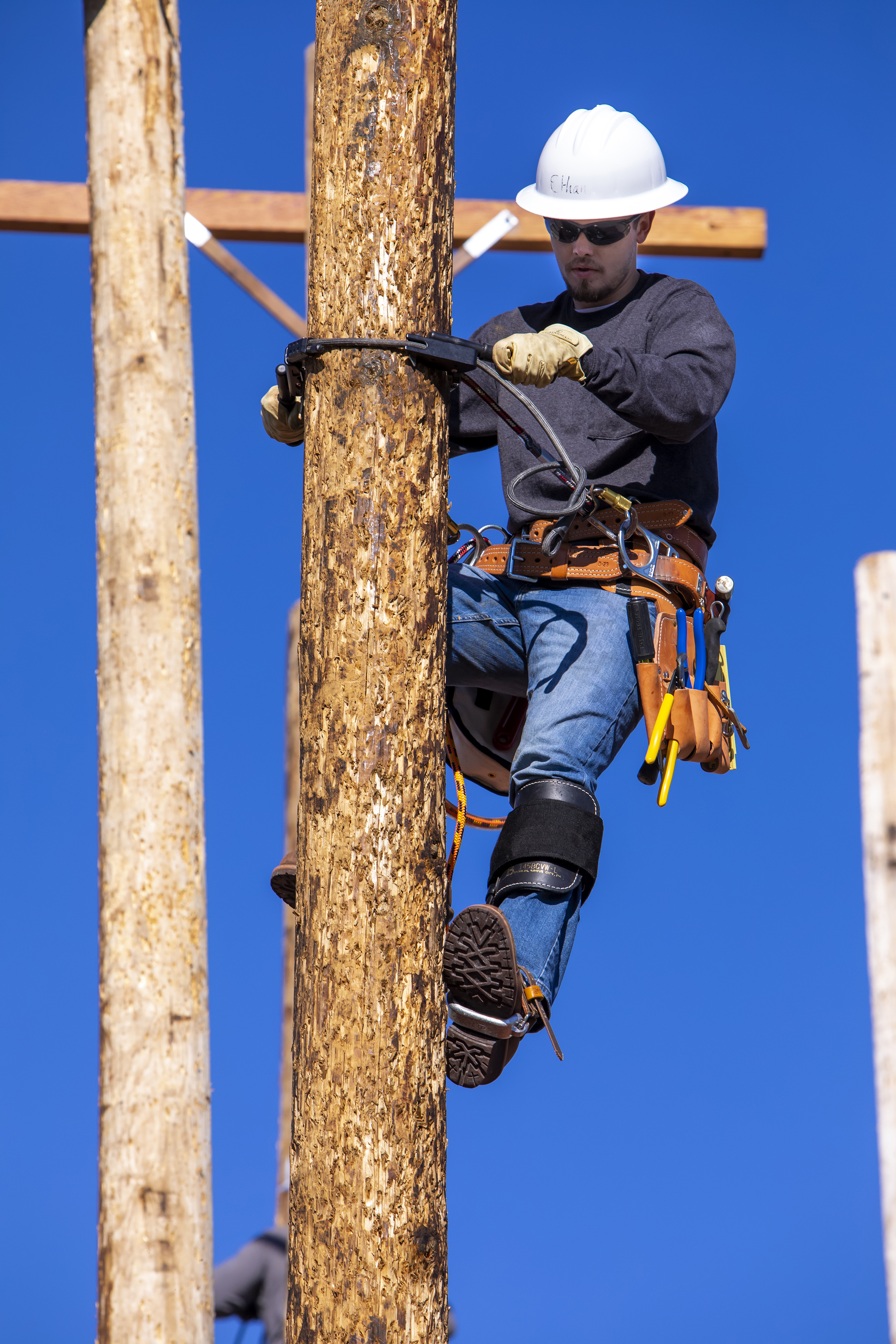 Ethan climbs a line worker pole