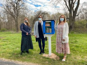 Volunteers stand by OTC's Free Little Library