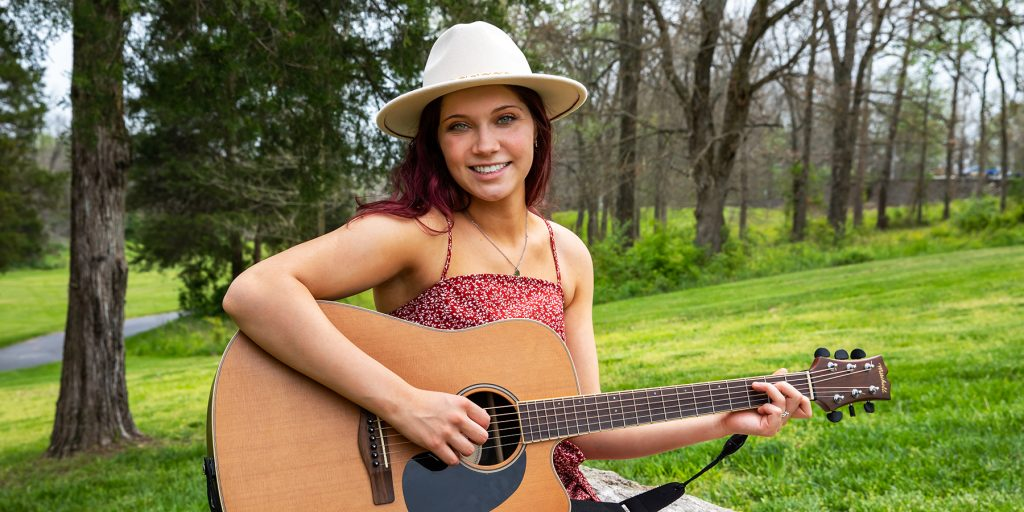 OTC student Riley Braker poses with her guitar outside the OTC Richwood Valley Campus